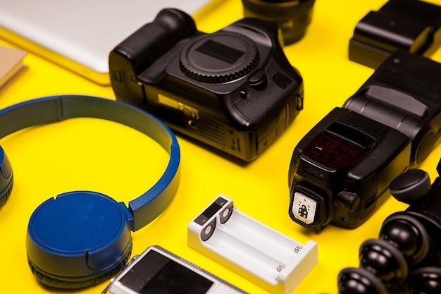 Пакет блоггера путешествия на желтом фоне. есть фотоаппарат, вспышка, зарядное устройство, наушники, штатив и ноутбук.