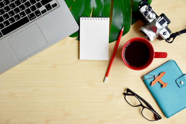 Travel blogger or writer work space, trip planning with laptop, blank notepad and camera