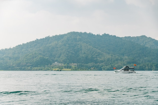 Travel boats floating over sun moon lake with mountain in background