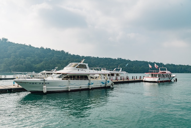 Travel boats stop at shuishe pier and floating over sun moon lake.