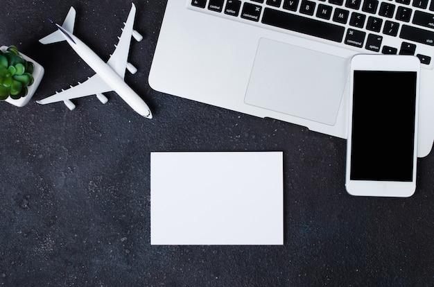 旅行予約のコンセプト。暗い背景にノートパソコン、白紙、スマートフォン、飛行機のモデル。