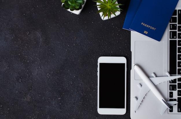 旅行予約のコンセプト。暗い背景にノートパソコン、パスポート、スマートフォン、飛行機のモデル。