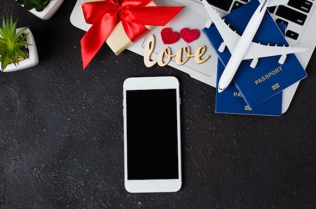 Концепция бронирования путешествий. смартфон, модель самолета, ноутбук, паспорта и подарочная коробка на темном фоне.