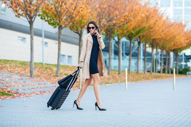 Travel, business woman in airport talking on the smartphone while walking with hand luggage in airport going to gate, girl using mobile phone for conversation