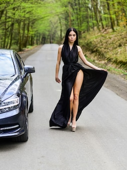Travel by car. auto and woman traveler. trip and wanderlust. hiking solo. vehicle selective focus. sexy woman go along road in fashion dress. travelling and wanderlust. pretty girl travel on foot.