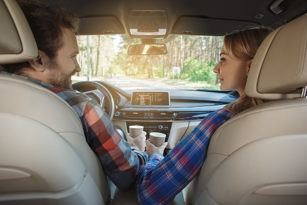 車で旅行家族が一緒にコーヒーを飲みながらカップルに乗る