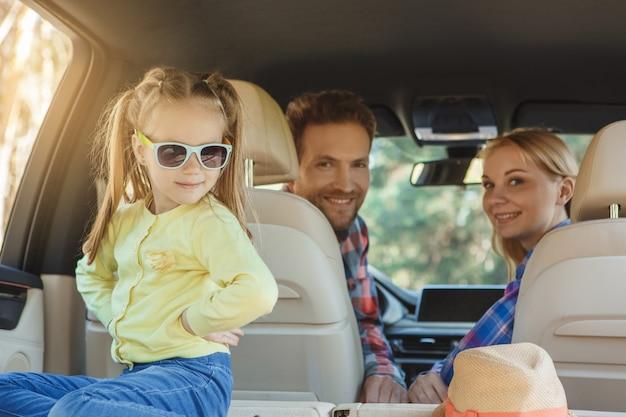 車で旅行家族が一緒にサングラスで遊ぶ娘に乗る