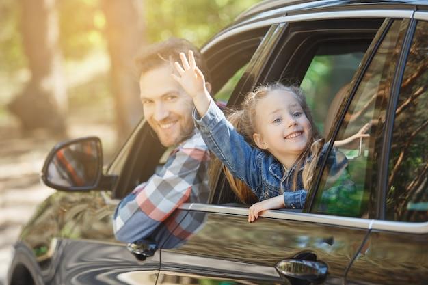 車での旅行家族が一緒に乗る父と娘が窓から身を乗り出す
