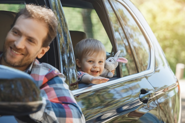 車での旅行家族が一緒に乗る父と息子が窓から身を乗り出す