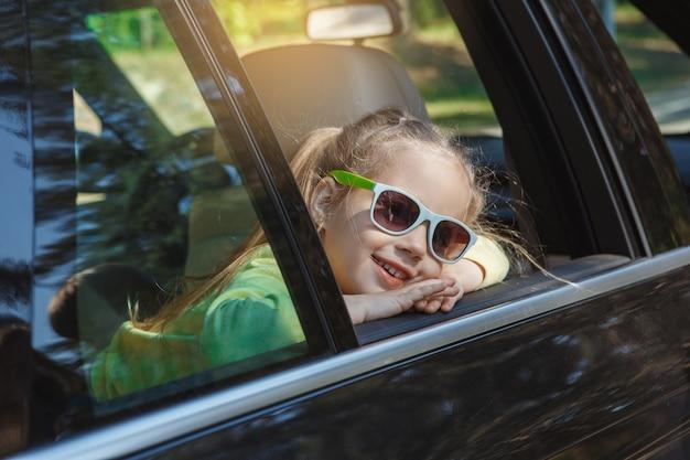 車で旅行家族が一緒にサングラスをかけている女の子に乗る