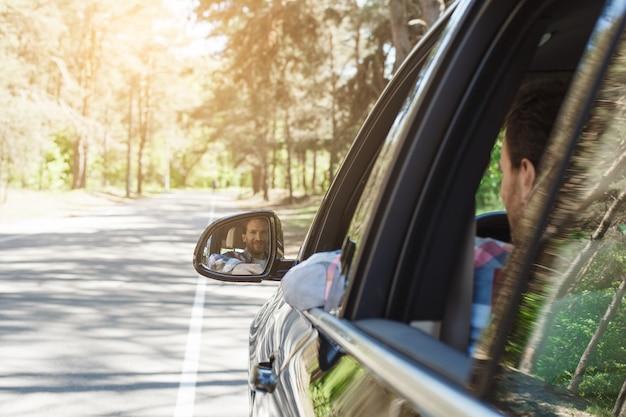 車での旅行家族が一緒に乗る鏡の反射