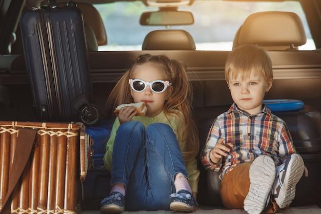 Путешествие на машине семья вместе брат и сестра, сидя в багажнике