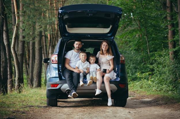 Путешествие на машине счастливая молодая семейная поездка вместе в отпуск. родители, папа и мама с симпатичными детьми рядом сидят в багажнике машины в кемпинге, отдыхают на пикнике, чтобы расслабиться в следующей поездке перед лесным походом