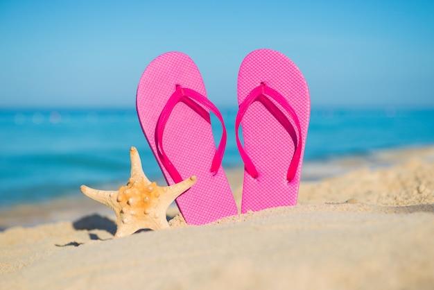 海で旅行します。ビーチでの休暇。砂浜の海岸にピンクのビーチサンダルとヒトデ。