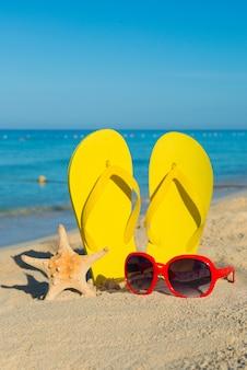 海で旅行します。ビーチでの休暇。砂浜の海岸に赤いサングラスと黄色のビーチサンダル。