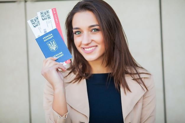 Путешествовать. веселая молодая женщина, держащая билеты на самолет на открытом воздухе