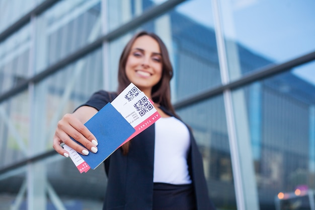 Travel. cheerful young woman holding plane tickets outdoors