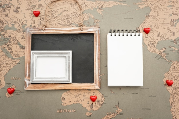 Travel composition with decorative hearts and blank notebook