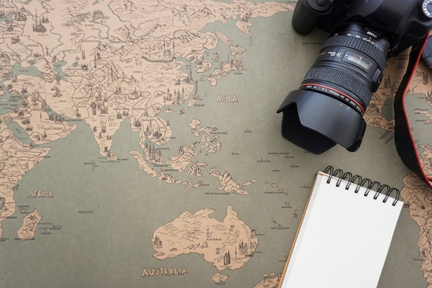 Travel composition with vintage map, camera and blank notebook