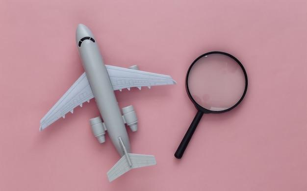 旅行のコンセプト。ピンクの飛行機と拡大鏡