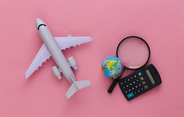 旅行のコンセプト。飛行機、地球儀の付いた拡大鏡、ピンクの電卓