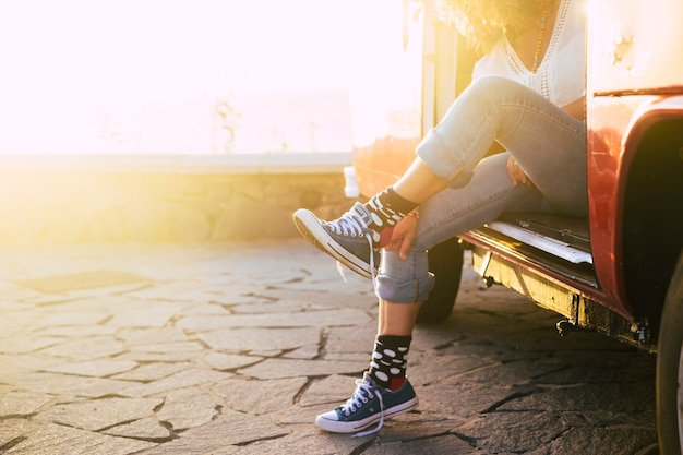 Travel concept for alternative vacation for people - woman with nice socks outside old vintage van with sunset sunlight - lady putting sneakers shoes