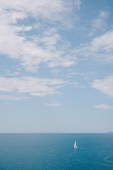 Фон концепции путешествия - небольшой парусник в море с голубым небом с облаками