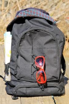 旅行のコンセプト。帽子、赤いサングラス、地図付きのバックパック