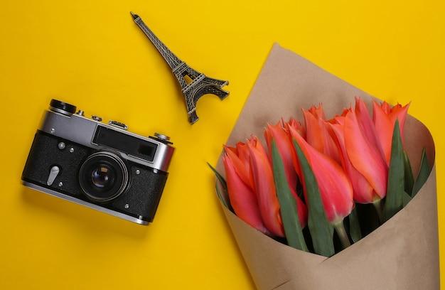 Концепция путешествия. букет тюльпанов, фотоаппарат, статуэтка эйфелевой башни на желтом.
