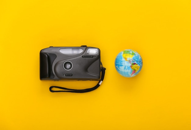 Travel concept. camera with a globe on yellow background. top view