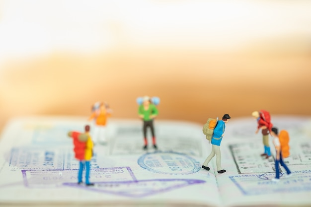 Travel concept. close up of group of traveler miniature figure with backpack walking and standing on passport with immigration stamped and copy space.
