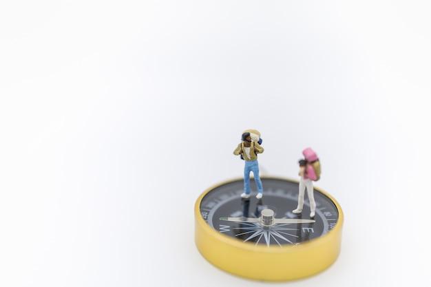 旅行のコンセプト。バックパックで2つの旅行者のミニチュアフィギュアのクローズアップ