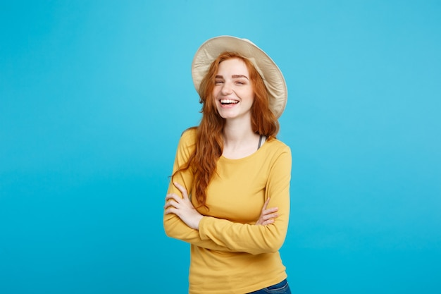 Travel concept  close up portrait young beautiful attractive ginger red hair girl with trendy hat and smiling blue pastel wall copy space