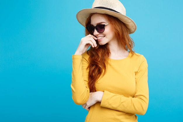 Travel concept - close up portrait young beautiful attractive ginger red hair girl with trendy hat and sunglass smiling. blue pastel background. copy space.