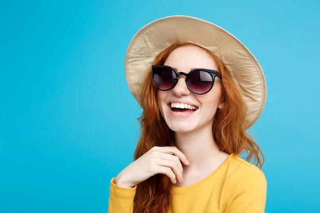 Концепция путешествия крупным планом портрет молодой красивой привлекательной рыжеволосой девушки с модной шляпой и солнцезащитными очками, улыбаясь синей пастельной стене копией пространства