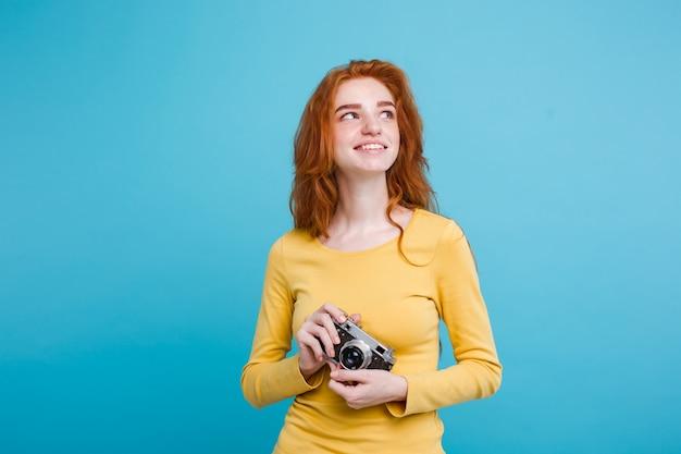 Concetto di viaggio - close up ritratto di giovane bella ragazza attraente redhair con cappello alla moda, sunglass e macchina fotografica d'epoca sorridente alla fotocamera. sfondo blu pastello. copia spazio.