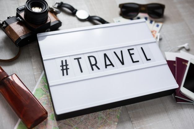 Travel concept  close up of travel objects and light box with hashtag travel