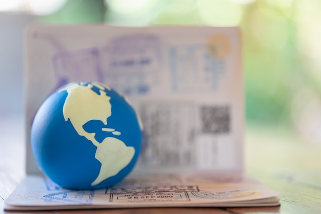Travel concept. closeup of mini world ball on passport with immigration stamped.