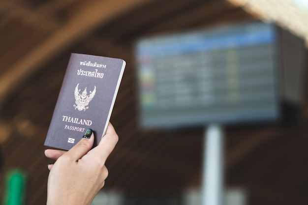 Travel concept. closeup of woman hand holding thai passport ready to boarding.