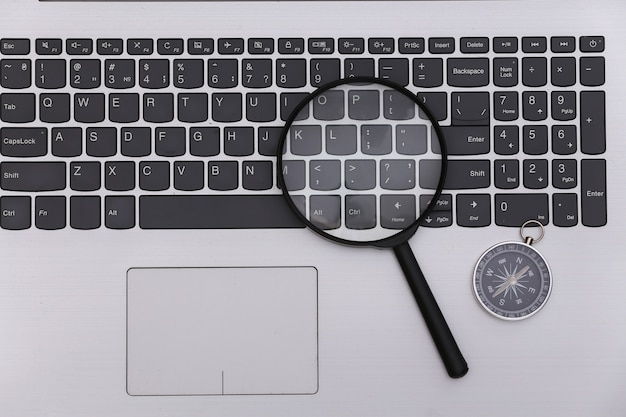 Travel concept. compass with a magnifier on a laptop keyboard