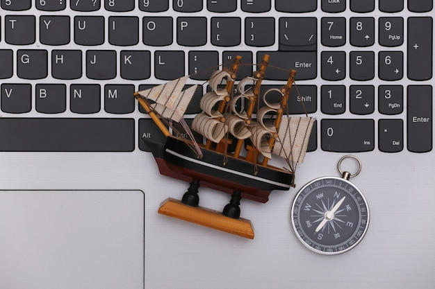 Travel concept. compass with ship on a laptop keyboard