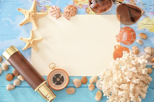 Концепция путешествия. композиция с бумагой и морскими раковинами на карте мира