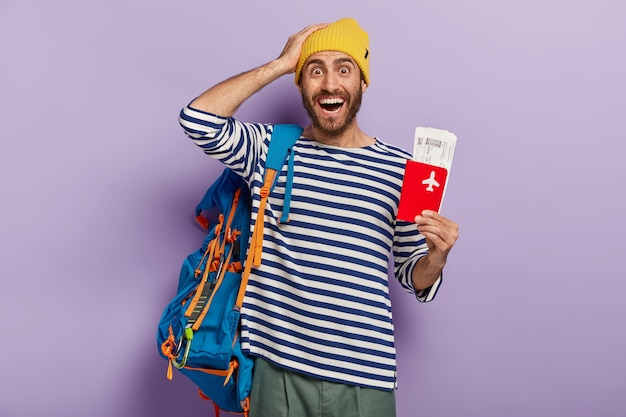 Travel concept. delighted man tourist rejoices voyage during summer holidays poses with travel ticket and documents arranges everything for traveling carries rucksack. backpacker has long awaited trip