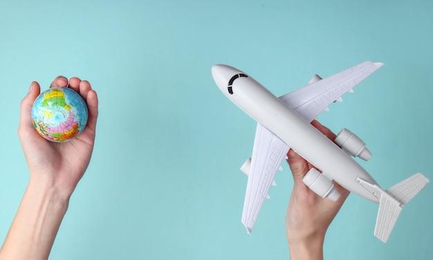 Концепция путешествия. женские руки держат глобус и фигурку пассажирского самолета на синем фоне