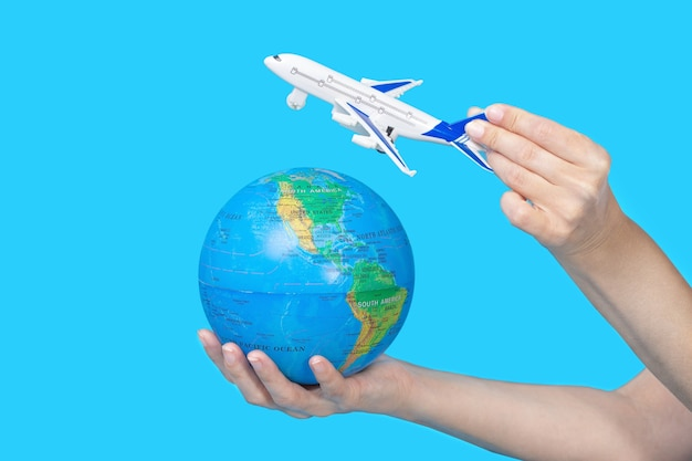 Travel concept. female hands holding globe and figurine of passenger plane on blue
