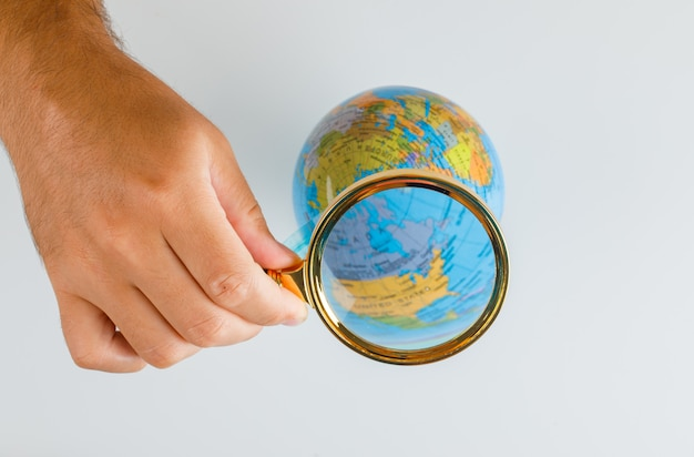 Travel concept flat lay. hand holding magnifying glass over globe.