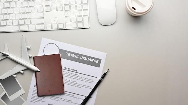 Travel concept flat lay workspace with passport insurance form computer devices travel items and copy space