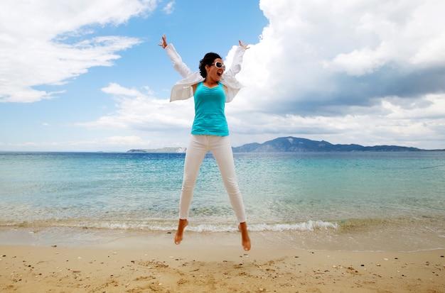 Концепция путешествия - счастливая девушка прыгает на пляже, летние каникулы