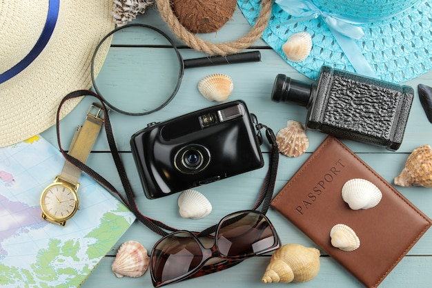 Travel concept hat, camera, passport, map and sunglasses on a wooden blue table. top view.