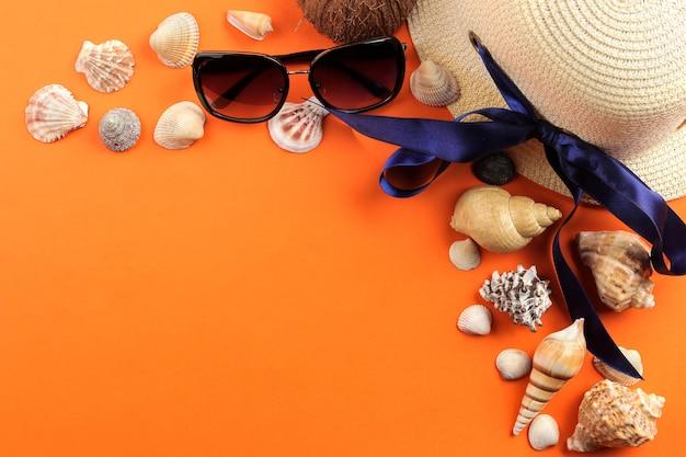 旅行のコンセプト明るいオレンジ色の背景に帽子、貝殻、サングラス。上面図。自由な場所
